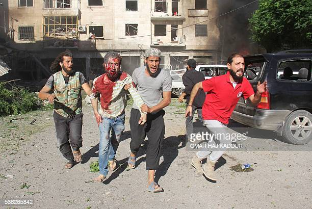 Graphic content / Syrians help an injured man following reported air strikes on a residential neighbourhood in the rebelheld northwestern city of...