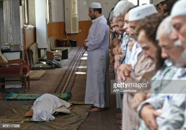 Graphic content / Syrians pray in a mosque over the body of a child who was reportedly killed during regime shellings in the rebelcontrolled town of...
