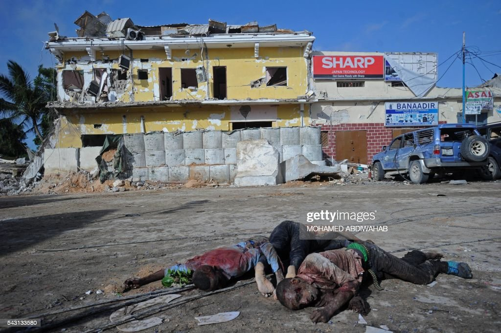 Graphic content / The bodies of three suspected fighters of the radical Islamist al-Shabab group lie in the road outside The Nasahablood Hotel in Mogadishu on June 26, 2016, a day after an attack in which at least 11 people were killed. At least 11 people were killed on June 25, 2016 in an attack on a hotel in the Somali capital Mogadishu that was swiftly claimed by Al-Qaeda-affiliated Shabaab militants. The assault, the latest in a series by the Islamist group targeting hotels and restaurants, began when a suicide bomber detonated a car laden with explosives outside the building. ABDIWAHAB