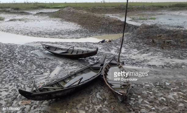 Graphic content / The body of a man lays in the mud after washing up during low tide on September 1 2017 after a boat capsized on the Naf river...