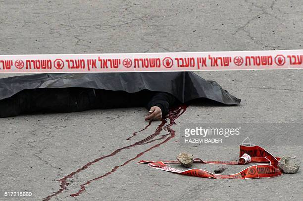 Graphic content / The body of a Palestinian assailant who was allegedly shot in the head by an Israeli soldier as he lay wounded on the ground after...