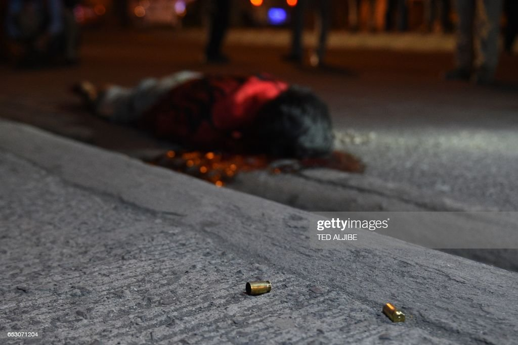 Graphic content / This photo taken March 9, 2017 shows empty bullet casings next to a body, who according to witnesses was thrown from a car and then shot several times by suspects, along a road in...