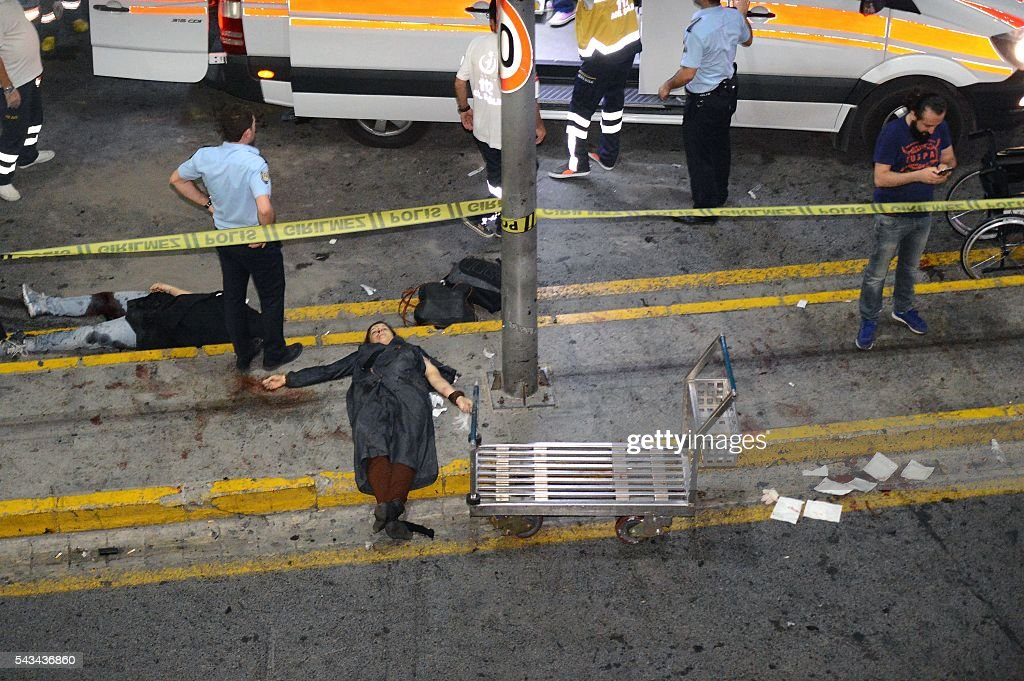 Graphic content / This picture obtained from the Ilhas News Agency shows ambulances and police intervening next to injured people lying on the ground, after two explosions followed by gunfire hit the Turkey's biggest airport of Ataturk in Istanbul, on June 28, 2016. At least 10 people were killed on June 28, 2016 evening in a suicide attack at the international terminal of Istanbul's Ataturk airport, Turkish Justice Minister Bekir Bozdag said. Turkey has been hit by a string of deadly attacks in the past year, blamed on both Kurdish rebels and the Islamic State jihadist group. / AFP / ILHAS NEWS AGENCY / - / Turkey OUT
