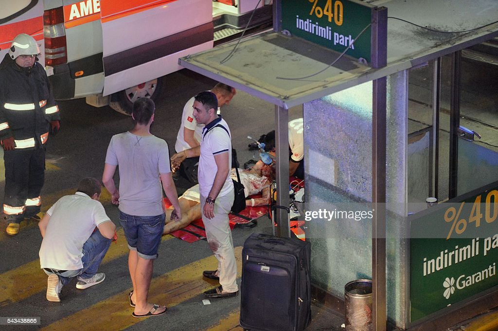 This picture obtained from the Ilhas News Agency shows emergency workers caring for an injured woman lying on the ground, after two explosions followed by gunfire hit the Turkey's biggest airport of Ataturk in Istanbul, on June 28, 2016. At least 10 people were killed on June 28, 2016 evening in a suicide attack at the international terminal of Istanbul's Ataturk airport, Turkish Justice Minister Bekir Bozdag said. Turkey has been hit by a string of deadly attacks in the past year, blamed on both Kurdish rebels and the Islamic State jihadist group. / AFP / ILHAS NEWS AGENCY / - / Turkey OUT