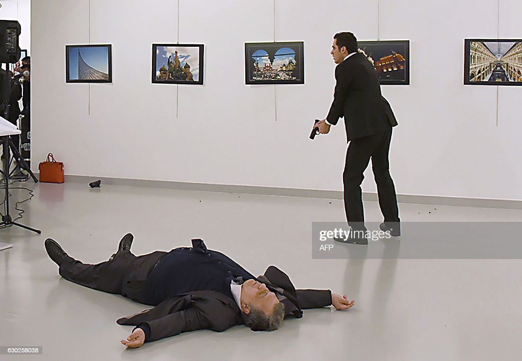 Graphic content / This picture taken on December 19, 2016 shows Andrei Karlov (L), the Russian ambassador to Ankara, lying on the floor after being shot by Mevlut Mert Altintas (R) during an attack during a public event in Ankara. A gunman crying 'Aleppo' and 'revenge' shot Karlov while he was visiting an art exhibition in Ankara on December 19, witnesses and media reports said. The Turkish state-run Anadolu news agency said the gunman had been 'neutralised' in a police operation, without giving further details. / AFP / Sozcu daily / Yavuz Alatan