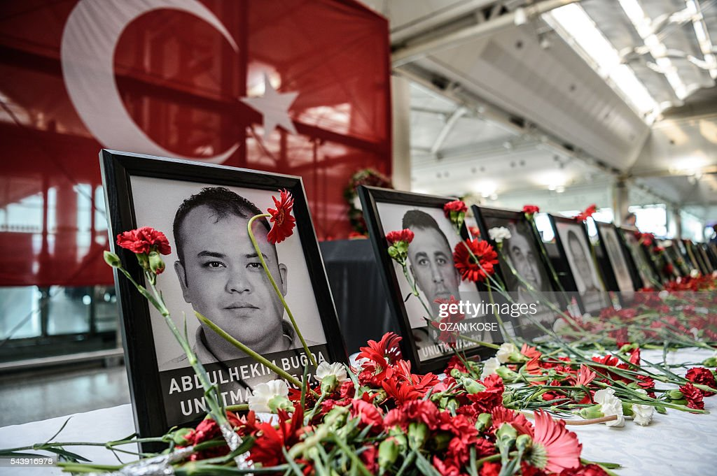 This picture taken on June 30, 2016 shows cloves left by airport employees next to killed airport employees pictures at Ataturk airport international terminal in Istanbul on June 30, 2016 two days after the triple suicide bombing and gun attack occurred at Istanbul's Ataturk airport. The death toll from the triple suicide bombing and gun attack that occurred on June 28, 2016 at Istanbul's Ataturk airport has risen to 43 including 19 foreigners. The government has pointed the finger of blame at the Islamic State group and Turkish police rounded up 13 suspected IS jihadists in raids at 16 different locations across Istanbul on June 30. / AFP / OZAN