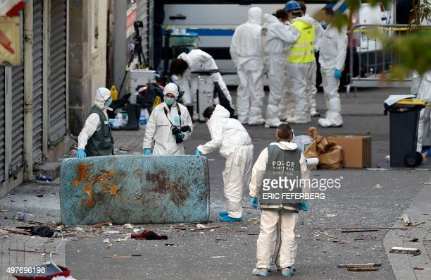 Graphic content / Forensics of the French police search for evidences next to the remains of a human head outside a building in the northern Paris...