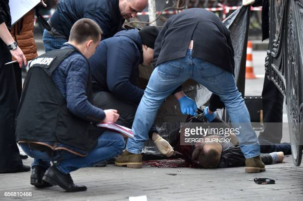 Graphic content / Ukrainian police experts examine the body of former Russian MP Denis Voronenkov after he was shot dead on March 23 2017 in the...