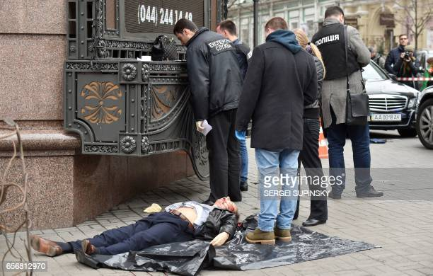 Graphic content / Ukrainian police experts look for evidence next to the body of former Russian MP Denis Voronenkov after he was shot dead on March...