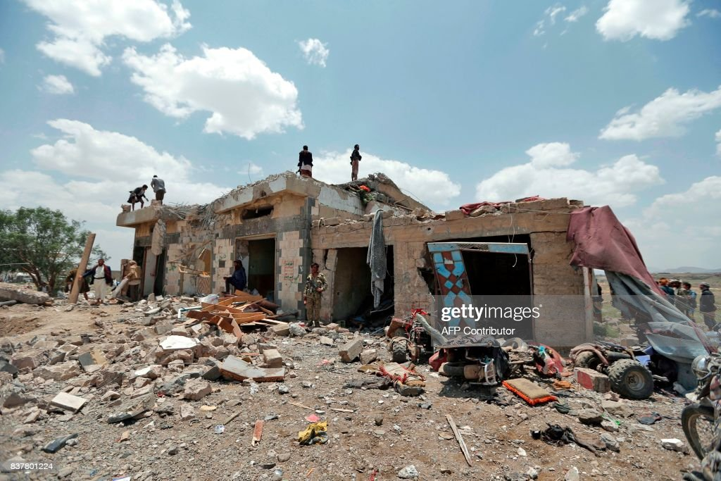 Graphic content / Yemenis stand at the site of an air raid in the Arhab area, around 20 kilometres (13 miles) north of Sanaa, on August 23, 2017, where a Saudi-lead coalition has been bombing Iran-backed Huthi rebels. The Huthis, who control Sanaa along with forces loyal to former president Ali Abdullah Saleh, blamed the pro-government Arab military coalition for the attack on Arhab district. / AFP PHOTO / Mohammed HUWAIS