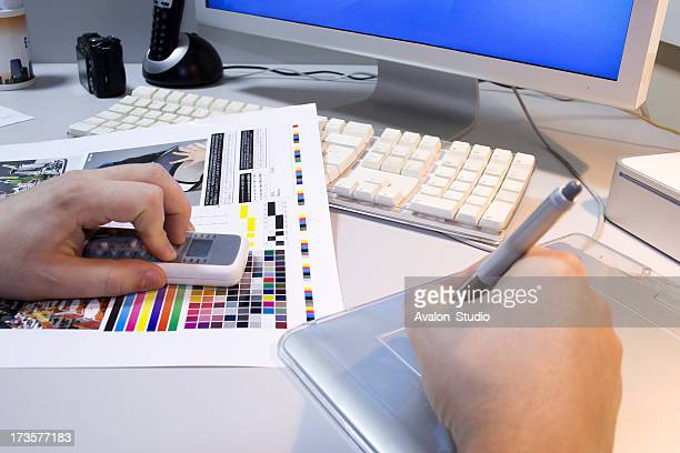 Graphic designer at work. Schedule checks the colors on the printout.