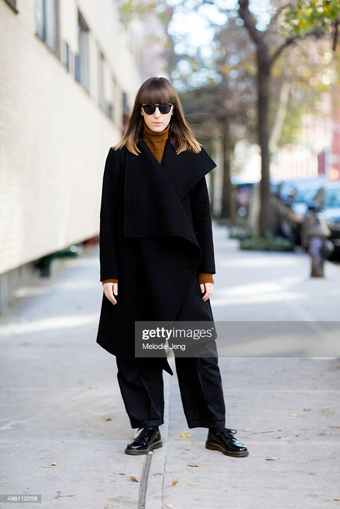 Graphic Designer Kelsey Fairhust wears an all black outfit with an OAK asymmetric woolfelt wrap Coat, orange Topshop turtleneck, Kowtow loose-fit cotton trousers, Doc Marten shoes, and Dior Homme sunglasses in Noho on November 20, 2015 in New York City.