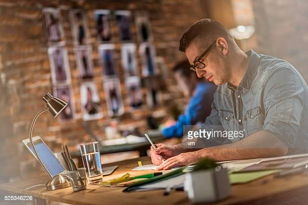 Graphic designer making sketches behind a desk