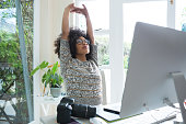 Graphic designer stretching her arms at desk