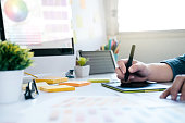 Graphic designer using graphics tablet to do work at desk