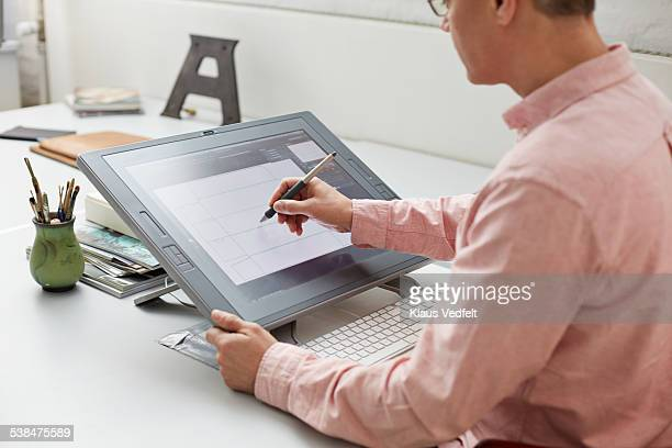 Graphic designer working on screen w. digital pen