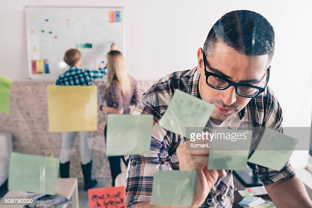 Graphic designers putting ideas on sticky notes on glass