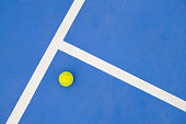 Graphic sports background of yellow tennis ball laying on blue floor in court, copy space