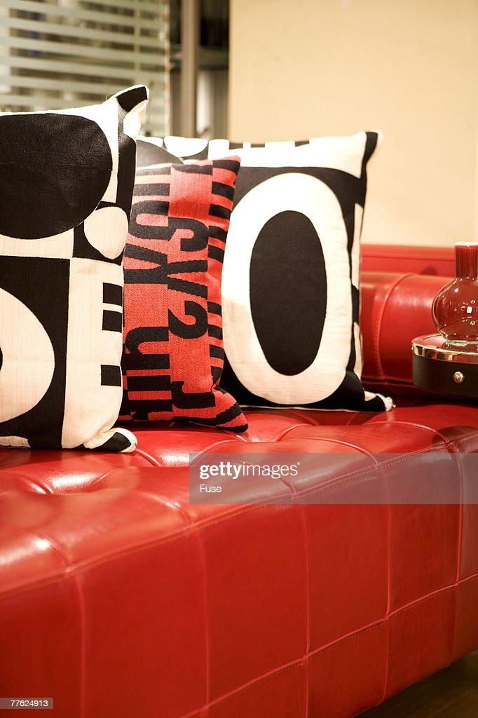 Graphic throw pillows on a red leather settee : Stock Photo