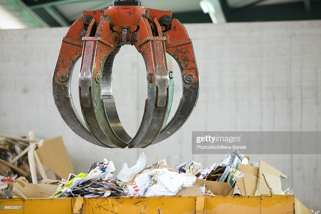 Grapple hanging over bin of waste paper in recycling center : Stock Photo