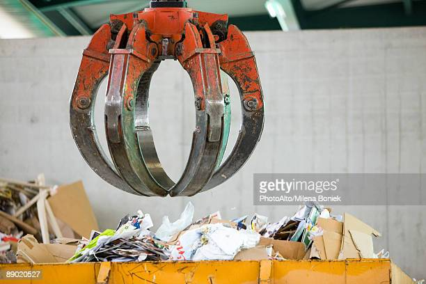 Grapple hanging over bin of waste paper in recycling center