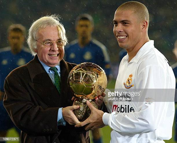 Gérard Ernault director of the magazine 'France Football' presents the Golden Ball trophy to Real Madrid's Brazilian forward Ronaldo before the...