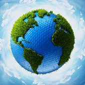 Grass covered globe with world map surrounded with blue sky showing Americas, Africa and Europe.