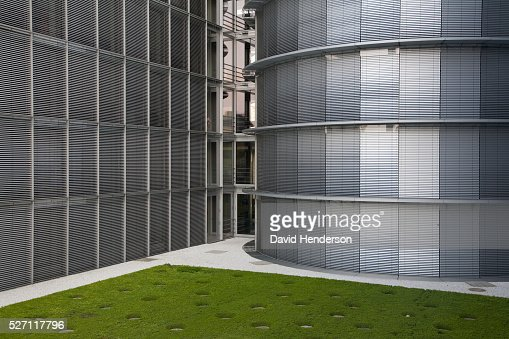 Grassy courtyard bordered by a curved metal wall : Stock-Foto