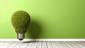 Grassy Light Bulb on Wooden Floor Against Green Wall with Copyspace 3D Illustration