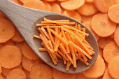Grated carrots in a wooden spoon