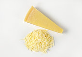 grated parmesan cheese and wedge on white background