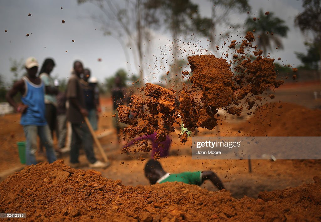 A grave digger works in the USbuilt cemetery for 'safe burials' on January 27 2015 in Disco Hill Liberia The cemetery operated by USAIDfunded Global...
