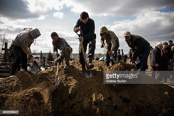 Grave diggers fill in the grave of Alexandrov Dimitri Vladimirovich a coal miner who was killed in a mine collapse at Zasyadtko mine on March 6 2015...