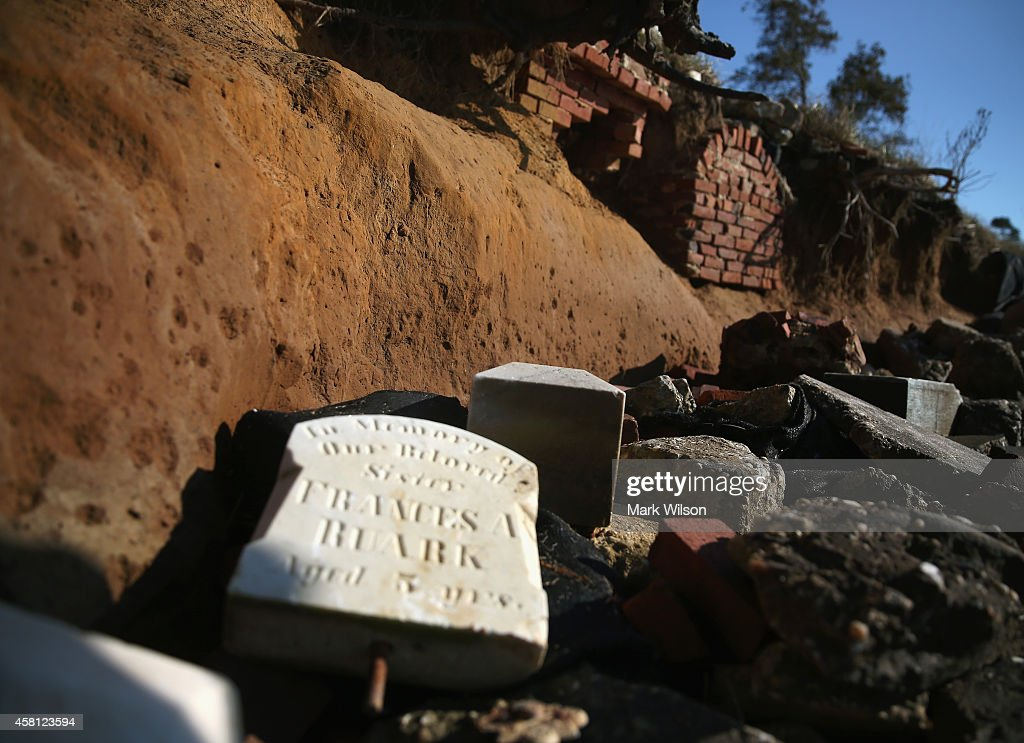 A grave marker and brick burial liners that were once several yards from the waters edge are now exposed and releasing human remains by the eroding...