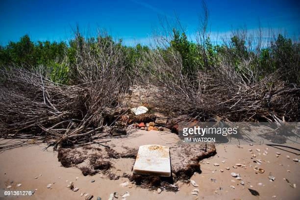 A grave stone rests on the beach where a cemetery once stood but has been washed away due to erosion in an area called Canaan in Tangier Virginia May...