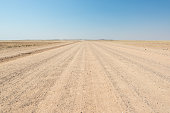 Gravel straight road crossing the colorful Namib desert, in the majestic Namib Naukluft National Park, best travel destination in Namibia, Africa.