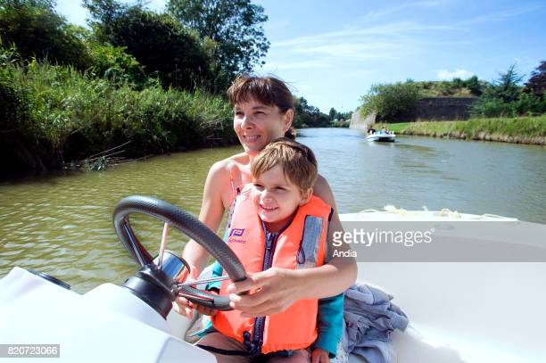 woman and her child on board an electric boat in the middle of the ramparts