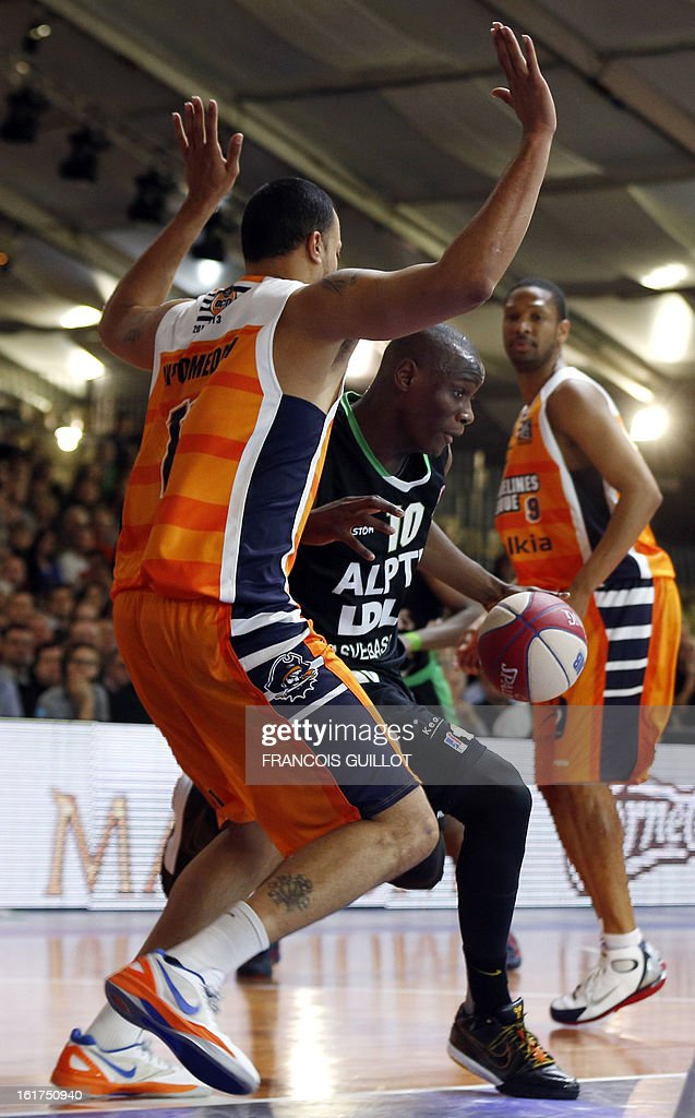 BCM Gravelines-Dunkerque player Cyril Akpomedah (L), vies with ASVEL Lyon-Villeurbanne player Amara Sy (C), during the leaders cup LNB 2013 tournament basketball quarter final match on February, 15, 2013 held at Disneyland Paris at Marne-la-Vallee near Paris.