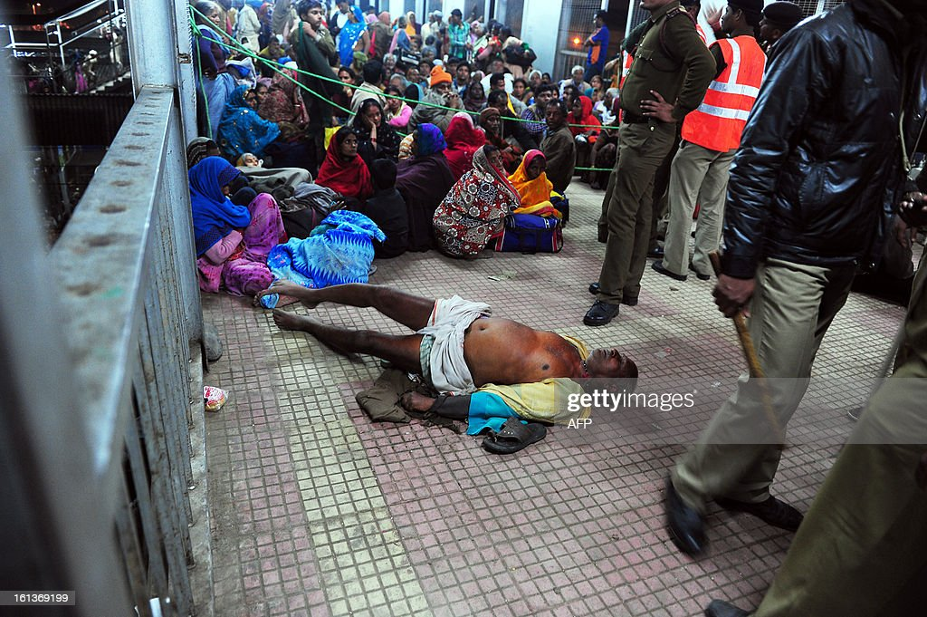 A gravely injured man that was crushed during a stampede lays on the concrete floor at the main train station in Allahabad on February 10, 2013 after a stampede killed at least 10 people at the main railway station serving India's giant Kumbh Mela festival. Dozens more were injured in the crush and some local television channels put the death toll as high as 20. Local officials said that the railings on a bridge at Allahabad station had given way under the pressure of the mass of people, while eyewitnesses told local media that the police had baton-charged the crowd leading to panic.