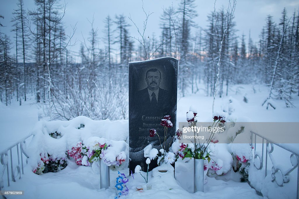 A gravestone for Vitaly Sayenko (1954-2008) stands covered in snow at the city cemetery near the mining town of Udachny, Sakha Republic, Russia, on Monday, Dec. 16, 2013. Russia plans to maintain control of Mirny-based Alrosa, which produces a quarter of the world's diamonds by value and more rough diamonds than De Beers by carat. Photographer: Andrey Rudakov/Bloomberg via Getty Images