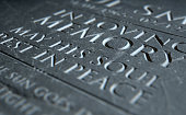 A 3D render of closeup of a carved and etched tombstone highlighting the word in loving memory