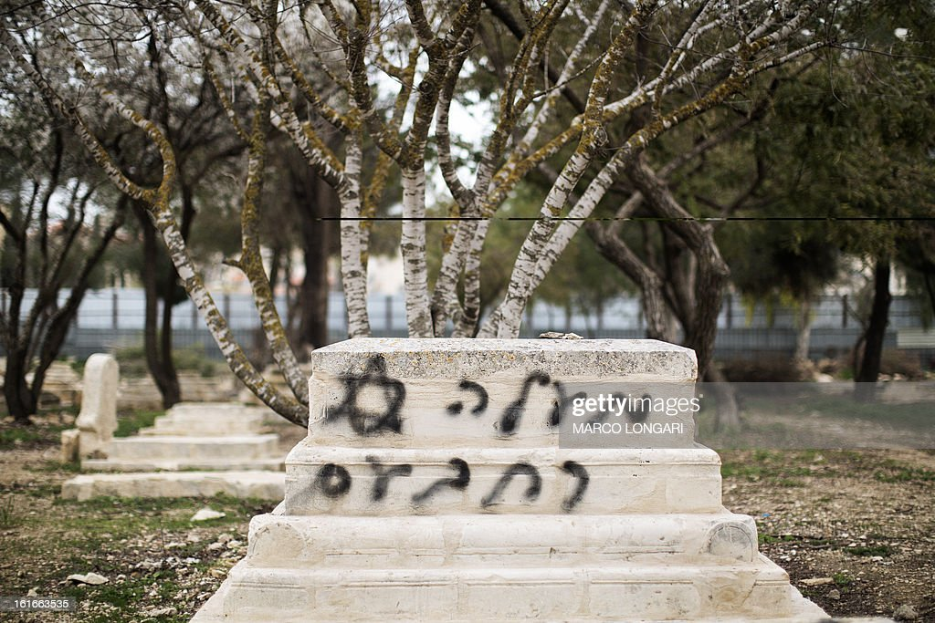 A gravestone is seen vandalised with spray paint with a graffiti reading in Hebrew: 'Maale Rehavam' (settlement) at the Mamun Allah cemetery, an old Muslim cemetery in Jerusalem on February 14, 2013. The price tag attack was an apparent revenge for the evacuation of the outpost of Maale Rehavam, destroyed yesterday by Israeli forces in the West Bank.
