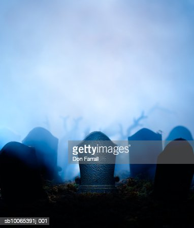 Graveyard at night with graves in mist