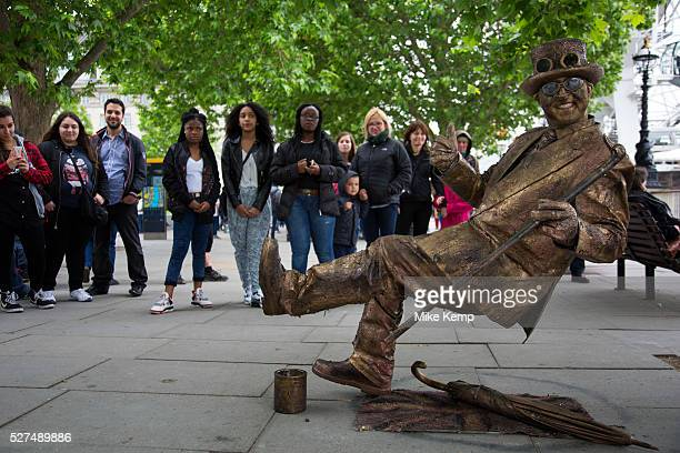 Gravity defying gold street performer entertains people on the riverside walkway The South Bank is a significant arts and entertainment district and...