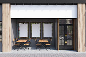 Exterior of a cafe with gray walls, three posters hanging on them and wooden tables with chairs. 3d rendering, mock up