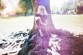 Gray haired woman taking break reading digital tablet in city park