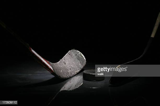 A gray hockey stick and a puck in solitude