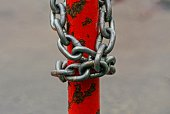 gray iron chain is wound on a red rusty pillar in the street