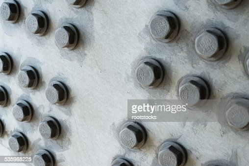 Gray metal surface with hexagonal bolt heads : Stock Photo