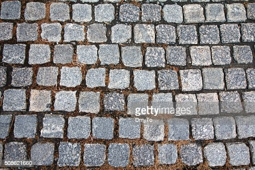 Gray paving stones and yellow grass. Backgrounds and textures : Stock Photo